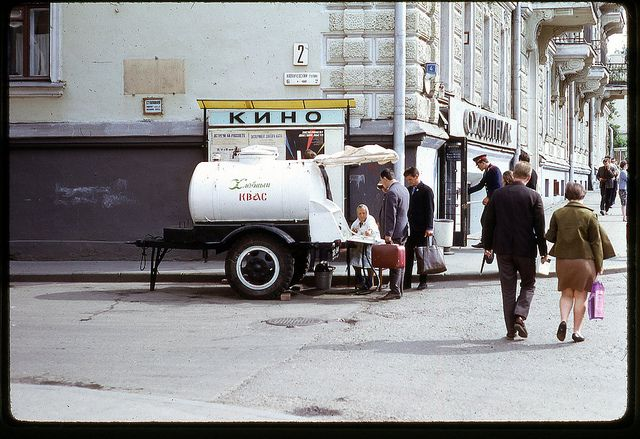 Kvas Street Vendor, Moscow, 1969 / The woman is selling kvass, a man in a military uniform is entering a hunting supply store.