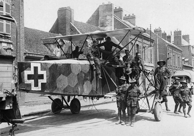 A downed German twin-engined bomber being towed through a street by Australian soldiers, France, World War I.