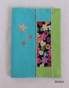 le protège carnet de santé avec une bande de patchwork soulignée d'un passepoil gris clair, couleurs dominantes bleu turquoise et vert anis, étoiles grises argentées