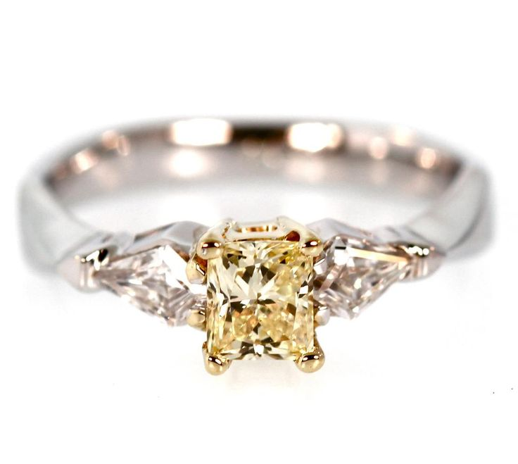 Flanked by two kite cut diamonds is a 1/2 carat natural fancy yellow radiant cut diamond. This ring is a custom design and crafted in 18k white gold.