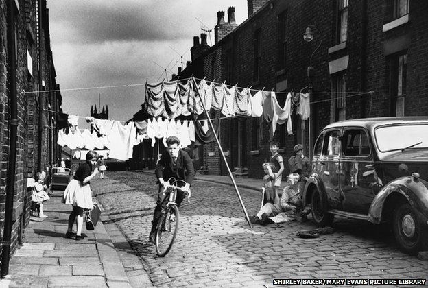 A boy cycles through the washing in a terraced street in Salford, Manchester, in 1962 by Shirley Baker