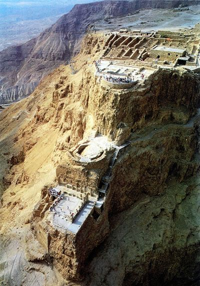HAVING Masada - Israel's mountain fortress constructed by King Herod; situated atop an isolated rock cliff at the western end of the Judean Desert, overlooking the Dead Sea; one route up is the Snake Path, a winding path that climbs 1,400 feet to the summit