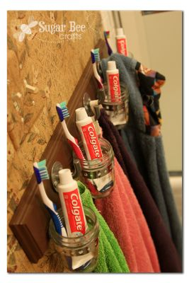 Organizers for not only the bathroom but my craftroom, too. Don't know if they used exhaust clamps or strapping with their mason jars; add a few hooks and walla!! This would be ideal for my paint brushes in the craft room!