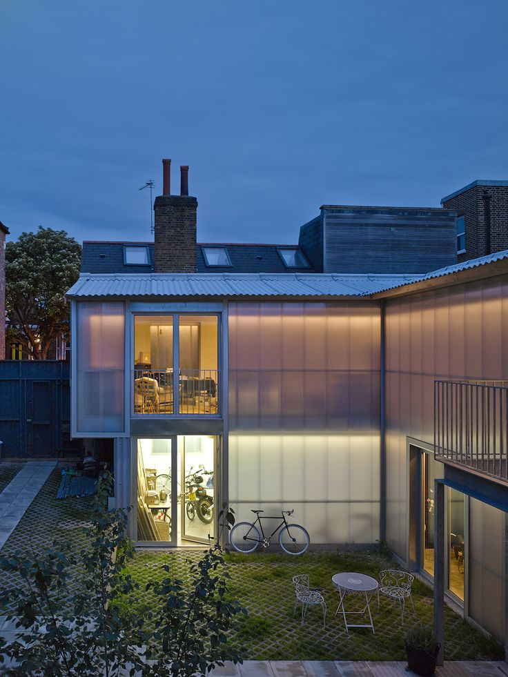 Yard House | Jonathan Tuckey Design, East Dulwich, London - Nighttime view of the exterior. The diffusion of light through the semi-translucent polycarbonate panels creates a warm glow.
