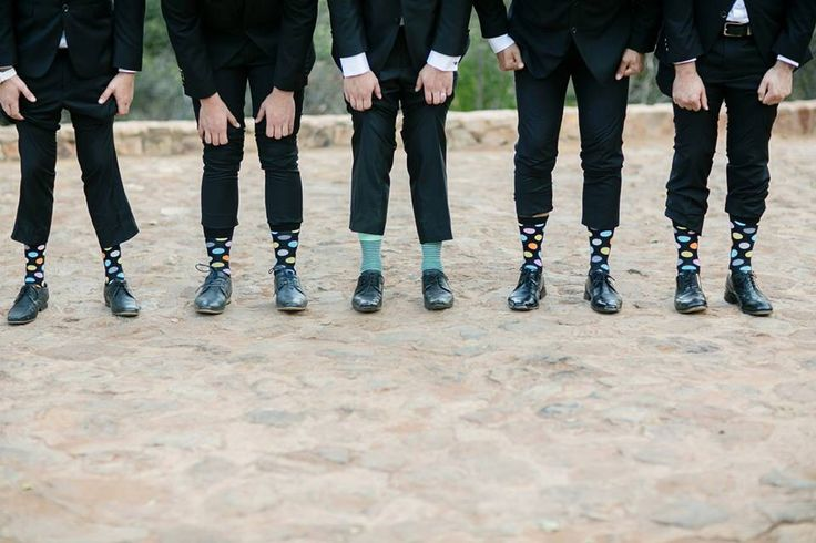 Wedding photography. Groom with his groomsmen all wearing coloured socks