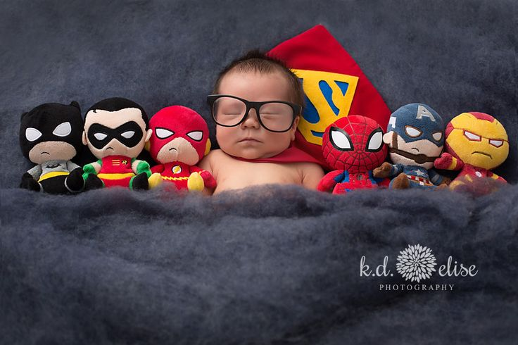 Newborn boy in Superman cape laying next to superhero stuffed animals. Superhero newborn session by Pueblo newborn photographer K.D. Elise Photography.