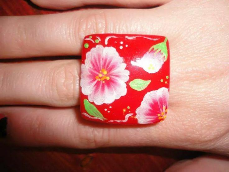 Anello fatto con gel per ricostruzione unghie rosso e decorato con pittura acrilica ad acqua.