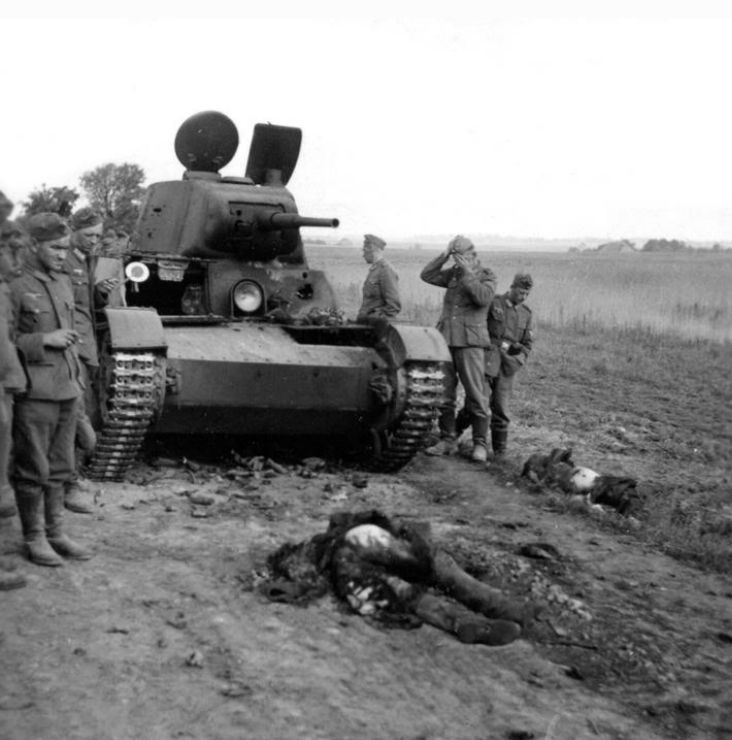 German soldiers view the result of anti-tank fire directed at a Russian tank.: Wwii