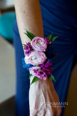 Pretty pink ranunculus and vibrant purple flowers on this wrist corsage with navy blue dress. | Door County Wedding | Best Bouquets of 2015 | Photo by Jason Mann Photography, 920-246-8106, www.jmannphoto.com