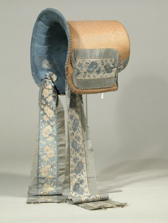Poke bonnet, 1815-1820. Made of narrow shiny straw plait lined with blue silk with an interlining of paper. The bonnet is trimmed with horsehair and straw plait braid and a wide band of blue and cream flowered ribbon pinned across the sides and under the crown. There are long ties of the same ribbon.