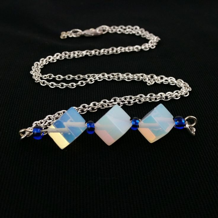 This is a striking blue and white necklace, an artisan bar necklace, a Sri Lanka Moonstone Necklace made from cubes of Sri Lanka Moonstone hand wire wrapped with cobalt blue Czech glass beads on silver plated wire. They are combined with a long silver plated chain. Bohemian Chic style, elegant, and minimalist all in one. This lovely artisan gemstone necklace in cobalt blue and iridescent moonstone would make a wonderful gift for any woman. Measures 25.5 long (65cm). The combination of three…