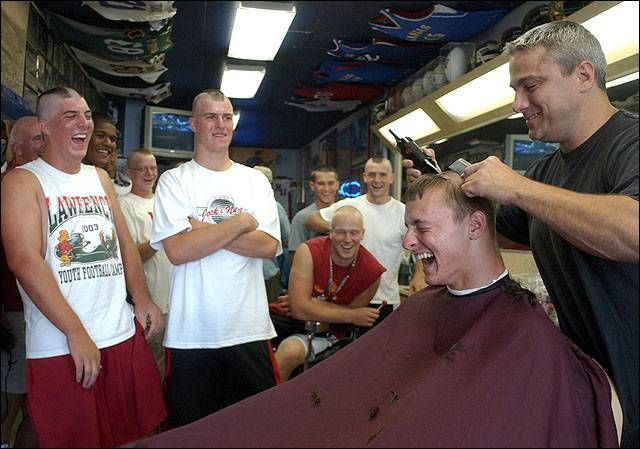 """Rex's Stadium Barber Shop, 1033 Massachusetts Ave, Lawrence, Kansas. It's been some variant of """"Stadium Barber Shop"""" since 1923. Present owner Rex Porter (above), formerly with Downtown Barber Shop, bought this place in 2004 from RC Pewtress, proprietor since 1987. Rex has kept it as a Kansas Jayhawks sports shrine. Here, he's shaving the heads of a dozen Lawrence High School football players prior to their 2005 season [Jared Soares photo]"""