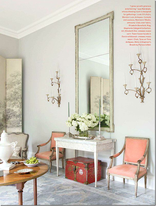 Randolph added his trademark soft pops of color with the apricot French chairs that were once placed across the room.  The walls are painted a gorgeous gray – Farrow and Ball Elephant's Breath.  While the chairs are antiques, the console and sconces are Niermann Weeks.