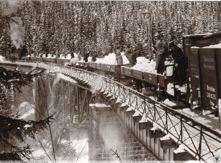 Robotnicy przymusowi i kolejarze zwalają śnieg z platform na Moście Izerskim na Dolnym Śląsku (marzec 1944)