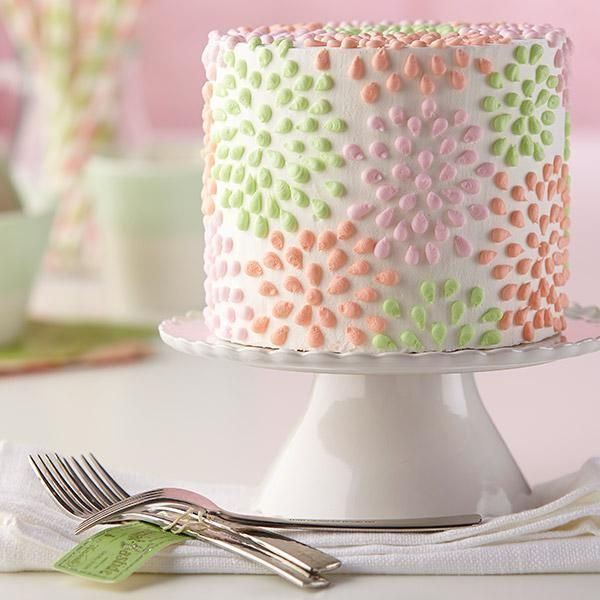 Polka-Dotted Flower Cake - Celebrate a brand-new spring season with this buttercream-iced cake decorated with colorful flowers piped using the bead technique. Learn how to do this simple technique and more by taking The Wilton Method of Cake Decorating Course 1.