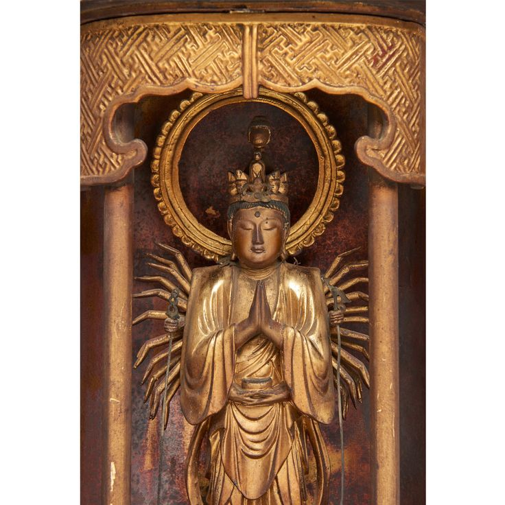 Black lacquered zushi-shrine, inside gilded. Each of the two doors of the shrine shows a crest: left the platycodon-flower (kikyō) of the Chisan-branch of the esoteric Shingon-school. Right an unidentified crest. Above a round lotus-throne stands a form of the Eleven Headed Kannon (Jūichimen Kannon. In Sanskrit: Ekadasamukha: the Jūichimen Senju Sengan Kannon, Kannon with…