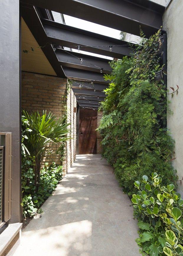Aclive no terreno dita arquitetura da casa. Paisagismo corredor de passagem (Foto: Maira Acayaba/Divulgação)