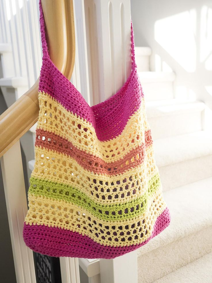 This quick and easy free Crochet Beach Tote Bag pattern is the perfect size for toting to the farmer's market, grocery store, or the beach. You can stash all your essentials in this cute pink, yellow, and green bag.