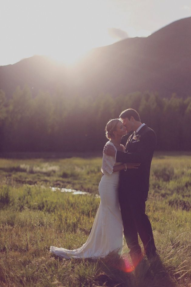 sweet whispers as the sun sets behind a mountain   rustic wedding photographed by Traci Griffin