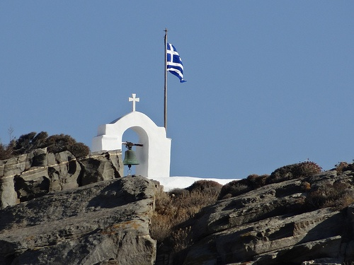 Church on a hilltop and the Greek flag