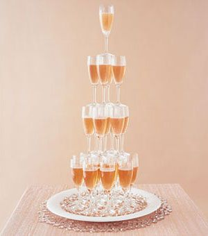 """Brides.com: Champagne Wedding Theme . Here, a Champagne-tower display really stacks up. """"SoHo"""" Champagne flutes are filled with rosé Champagne. Flutes, from TriServe Party Rentals, NYC and Southampton, NY, triservepartyrentals.com."""