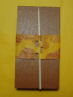 This book I covered with a faux wood patterned paper. The yellow notched cigar wrap is a printed fabric paper. The wood dowel is simply a kebab skewer.