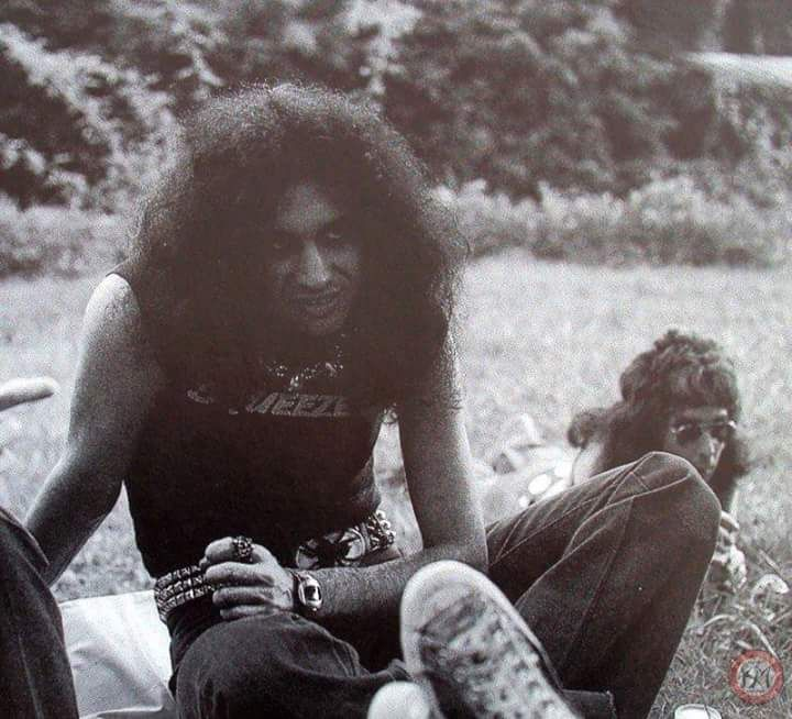 An early pic of Gene Simmons of KISS chillin in a field, Peter Criss in the back. Must be 74 - 76?