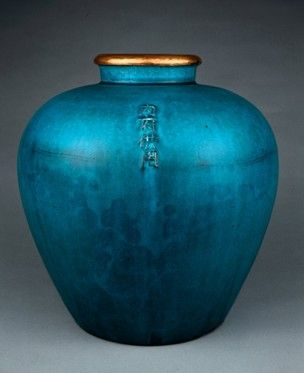 Porcellaneous stoneware wine-jar of guan form, with ovoid body and gilt copper-bound mouth rim. Finely crazed turquoise glaze. Inscription on shoulder.