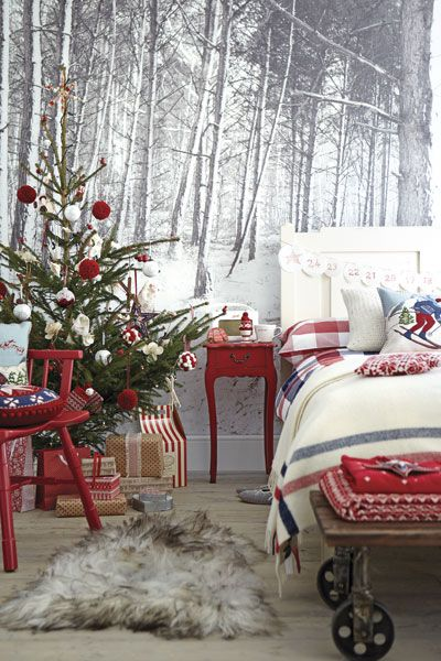 For a truly festive scheme in the bedroom, try this Skandi ski-lodge look. A woodland mural sets the scene for a real fir tree trimmed with traditional decorations.