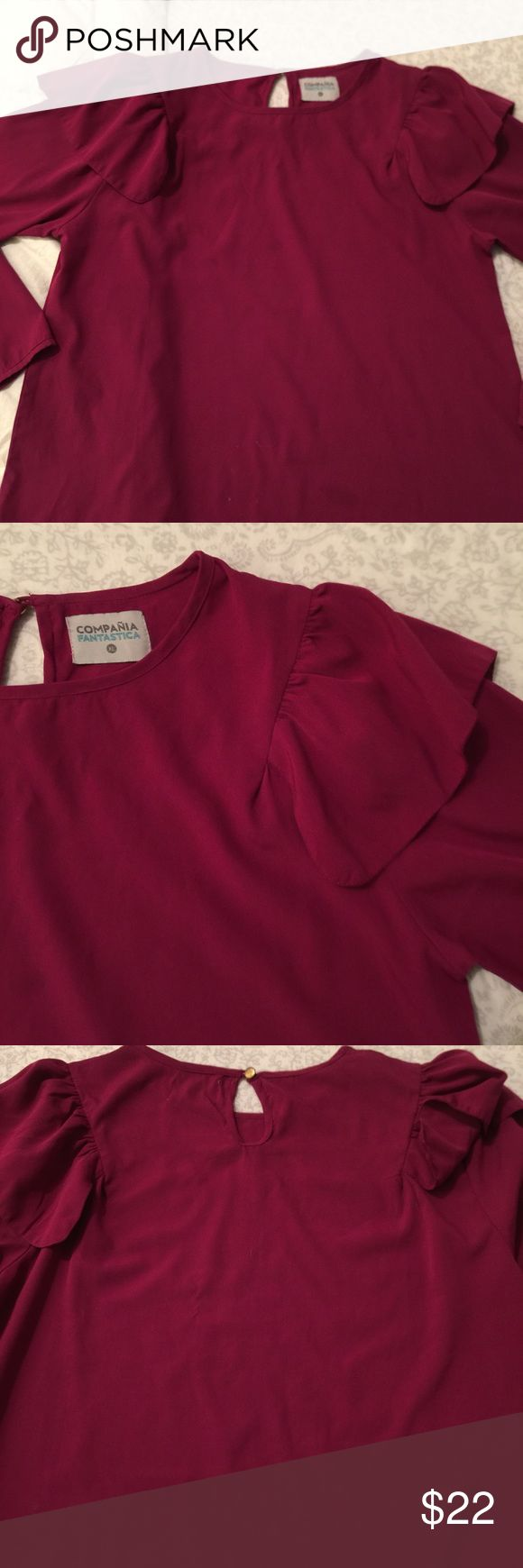 Compania Fantastica fancy top from lord n Taylor Very beautiful only wore it one time to an event. Magenta colored dress top. The most adorable and unique ruffled sleeve. It is an XL but fit very comfortably at a size med/large. Bought at lord and Taylor Compania Fantastica Tops Blouses