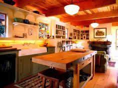 """Practically every inch of this kitchen is made of reclaimed wood: The wall cladding came from a salvage yard; the ceiling and the island's big timber top were constructed from beams from an old warehouse; the fireplace mantel is an old piece of natural-patina timber that was left outside to weather; and the 1"""" x 12"""" flooring is salvaged fir. Even the enameled cast-iron kitchen sink was a find the homeowners brought with them from their previous home."""