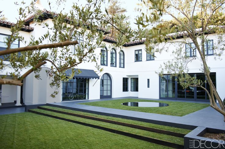 The rear garden is lined with basalt stone, and the awning is of a Sunbrella fabric.   - ELLEDecor.com