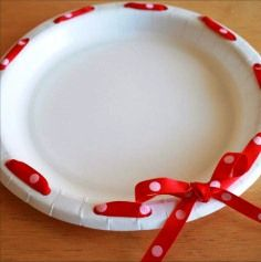 dress up paper plates with a hole punch and some ribbon -