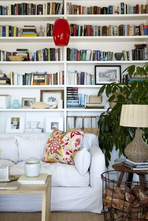 Love sofas backed up to shelving and dig the wire basket full of wood cuts.