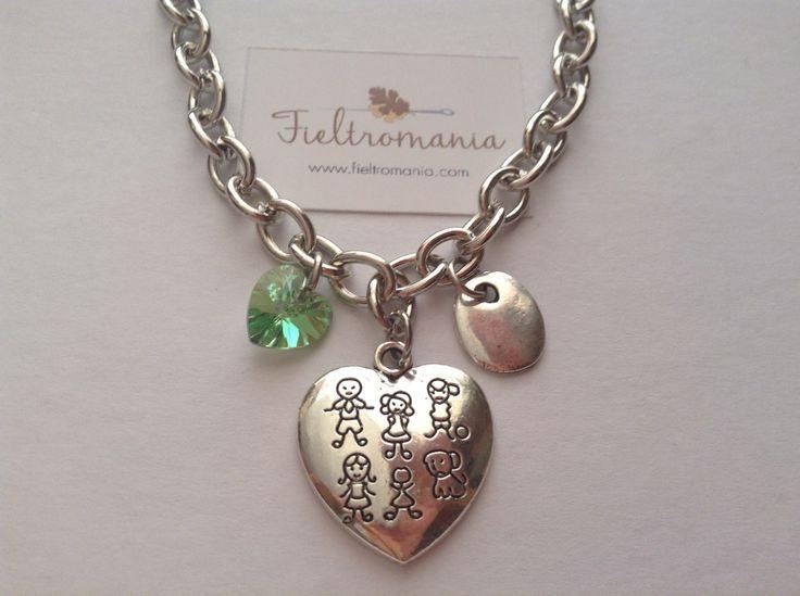 Colgante Corazón Familia Colgante Medalla Corazón Familia (22 x 20 mm) con colgante plano bañado en plata y corazón de cristal Swarovski a elegir en color rosa, verde o ámbar.