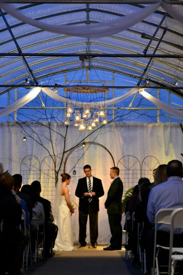 Greenhouse wedding at Scheiderer Farms.  Branches from the woods, mason jar chandeliers, and hundreds of candles gave it a warm rustic feel.