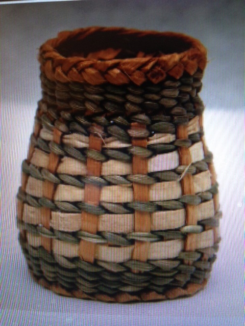 """Spiral Mini Basket Peggy Wilcox Made with a hex start using Cedar inner bark spokes. A foot added to the base, spiral up with bark and Japanese Iris leaves, then finished with a woven border. 1-5/8""""W x 1-5/8""""L x 2"""" H"""