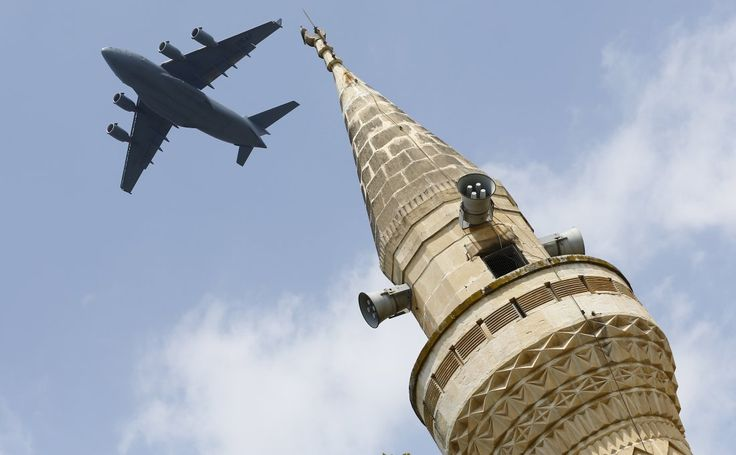 A U.S. Air Force Boeing C-17A Globemaster III large transport aircraft flies over a minaret after taking off from Incirlik air base in Adana