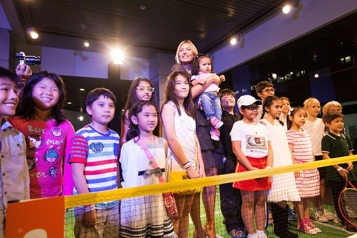 Maria Sharapova Photos: Charity Event with Porsche Asia Pacific In Singapore. Maria Sharapova Maria Sharapova, wearing a Chloe dress, Kurt Geiger shoes and a watch by TAG Heuer, poses with children as she attends a charity event with Porsche Asia Pacific on October 16, 2014 in Singapore.