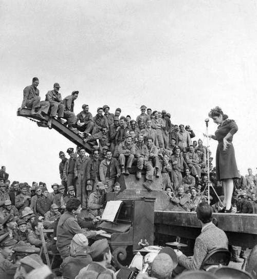 Comedian Martha Raye on stage for a rapt audience of American soldiers during a USO-Camp Shows, Inc. tour of U.S. Army camps in North Africa. Photograph by Margaret Bourke-White. North Africa, 1943.
