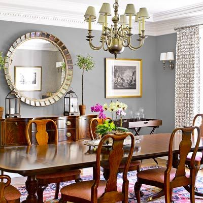 The dining room is anchored by vintage finds and enlivened by an oversize mirror and chandelier.