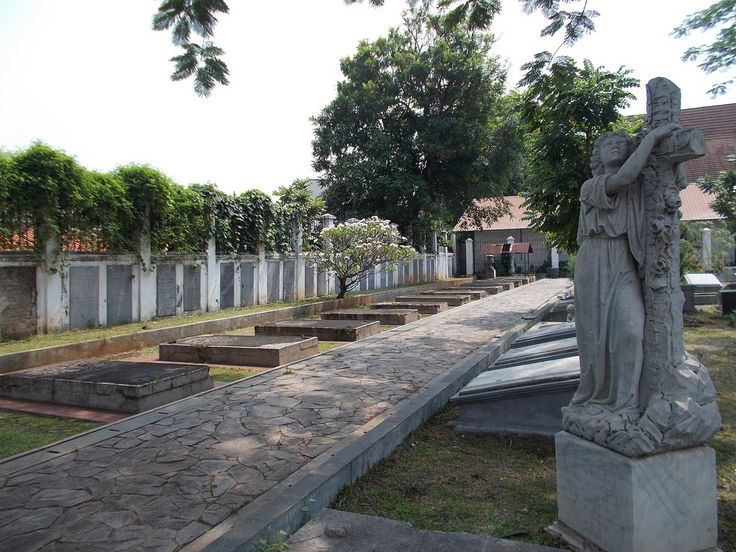 The scenery of Museum Taman Prasasti, Jakarta. An angel statue stands and holds a cross beside a row of tombs.
