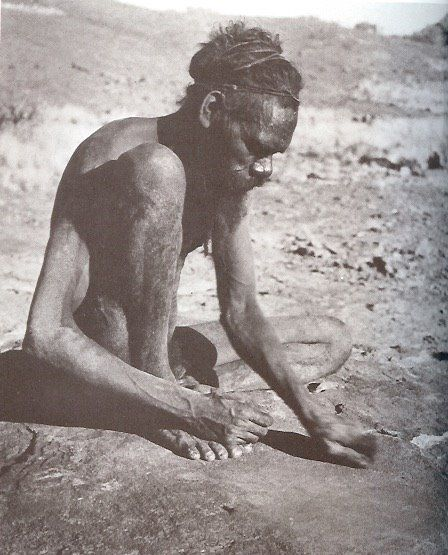 Man grinding ochre to decorate himself. From Nomads of the Australian Desert by Charles P. Mountford, 1976.