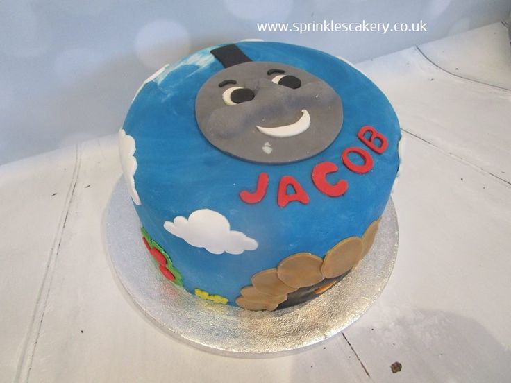 A simple Thomas the Tank Engine design with clouds and a tunnel made using fondant cutters wrapping around the cake.