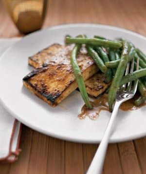 Thai Spiced Tofu  8  ounces  firm tofu, cut into four 1/2-inch slices  3  tablespoons  Thai red curry paste (found in the Asian section of most supermarkets)  3  tablespoons  sugar  2  tablespoons  fish sauce (or tamari, for vegetarians who don't eat fish)  1/2  pound  green beans  1/2  cup  vegetable broth  1  tablespoon  peanut oil