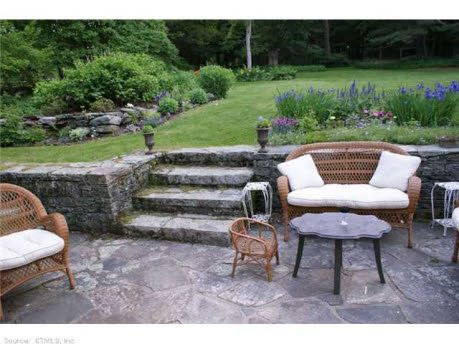 Beautiful stone sunken patio surrounded by gardens. Find this home on Realtor.com