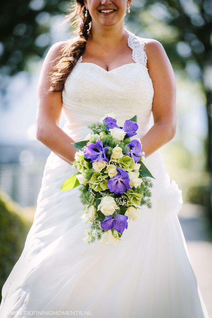 Bruidsboeket met paarse orchideeën en witte rozen, afgewerkt met sierlijk groen. Wedding bouquet with purple orchids and white roses.
