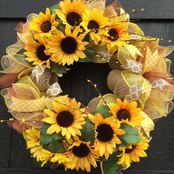Sunflower Wreath This wildly popular Sunflower Wreath will make you feel like walking on sunshine. The wreath is made of a natural poly jute mesh, and trimmed with yellow and copper deco mesh. The wreath is accented with various coordinating dovetailed ribbons; including a canvas and white quatrefoil, yellow and white check, and a yellow and white polka dot. #sunflowerwreath #burlapwreath, #homedecor