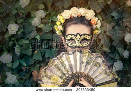 Beautiful Woman with Floral Wreath, Mask and Fan - Portrait of a mysterious masked woman holding a fan  - stock photo
