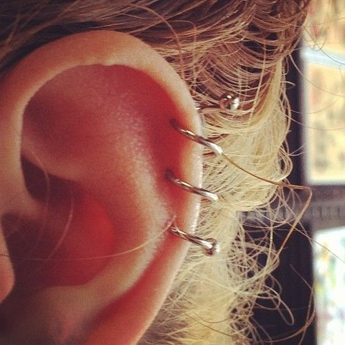 Triple spiral Helix piercing. This perfectly healed piercing was performed by Ch...